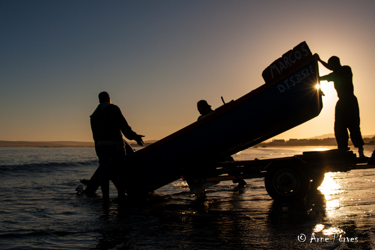 Rock lobster fishermen launch their boat off the beach