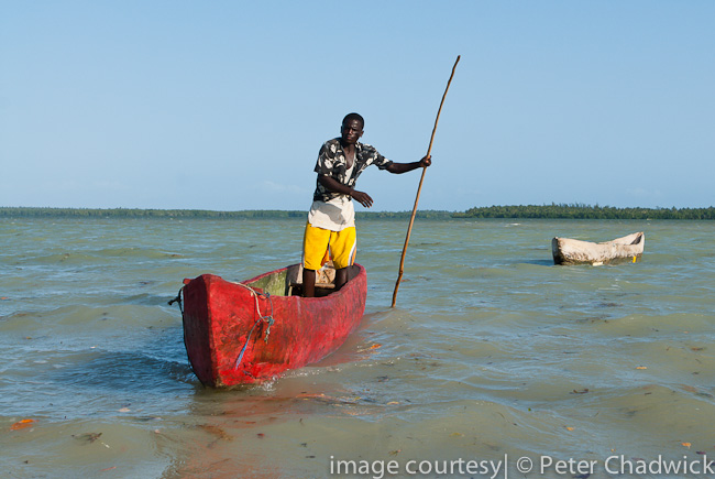 polesman and dugout canoes at mida creek by wildlife and conservation photographer peter chadwick