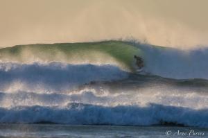 A Surfer Tucks Into A Cold Atlantic Barrel